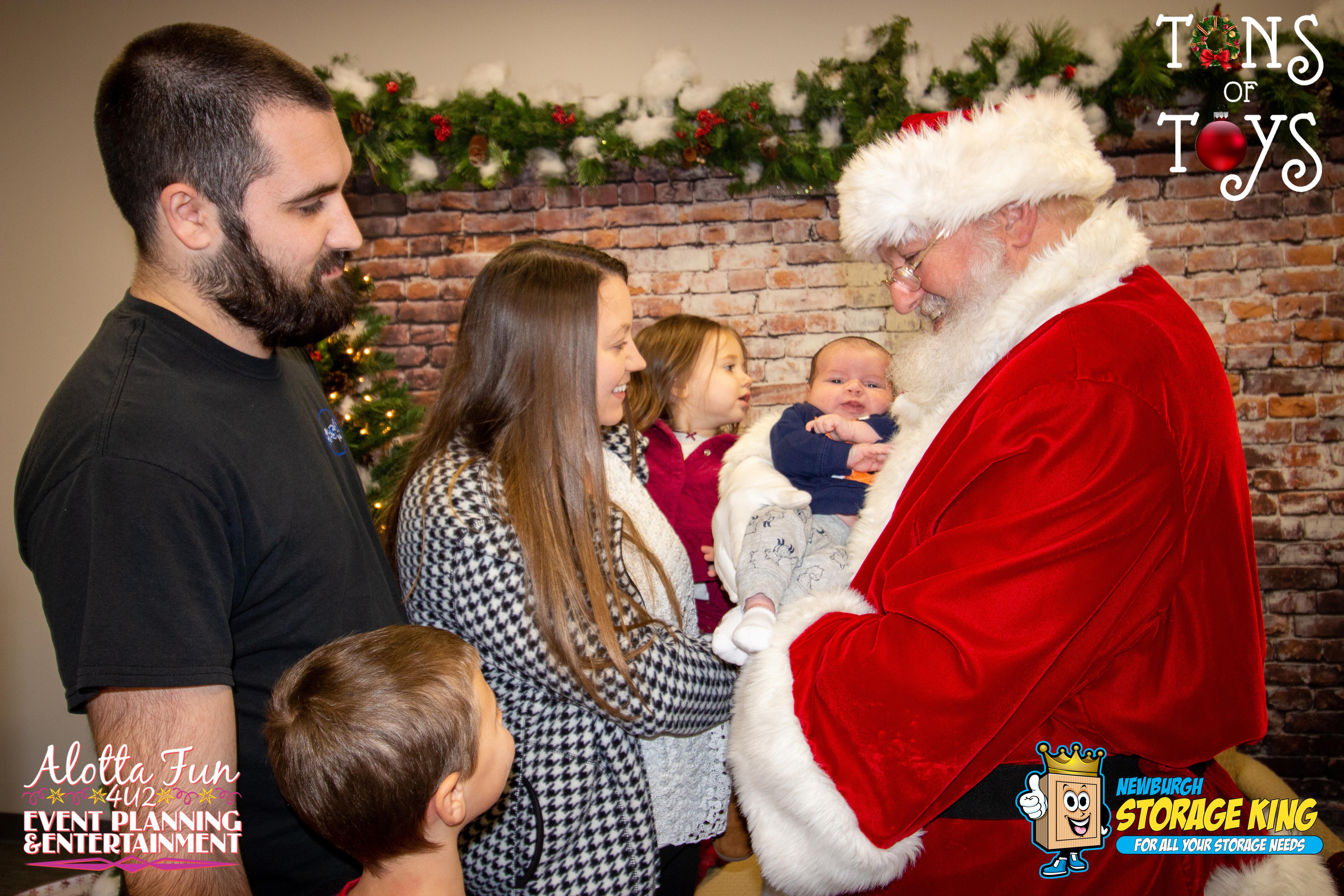 family gathered around santa holding baby