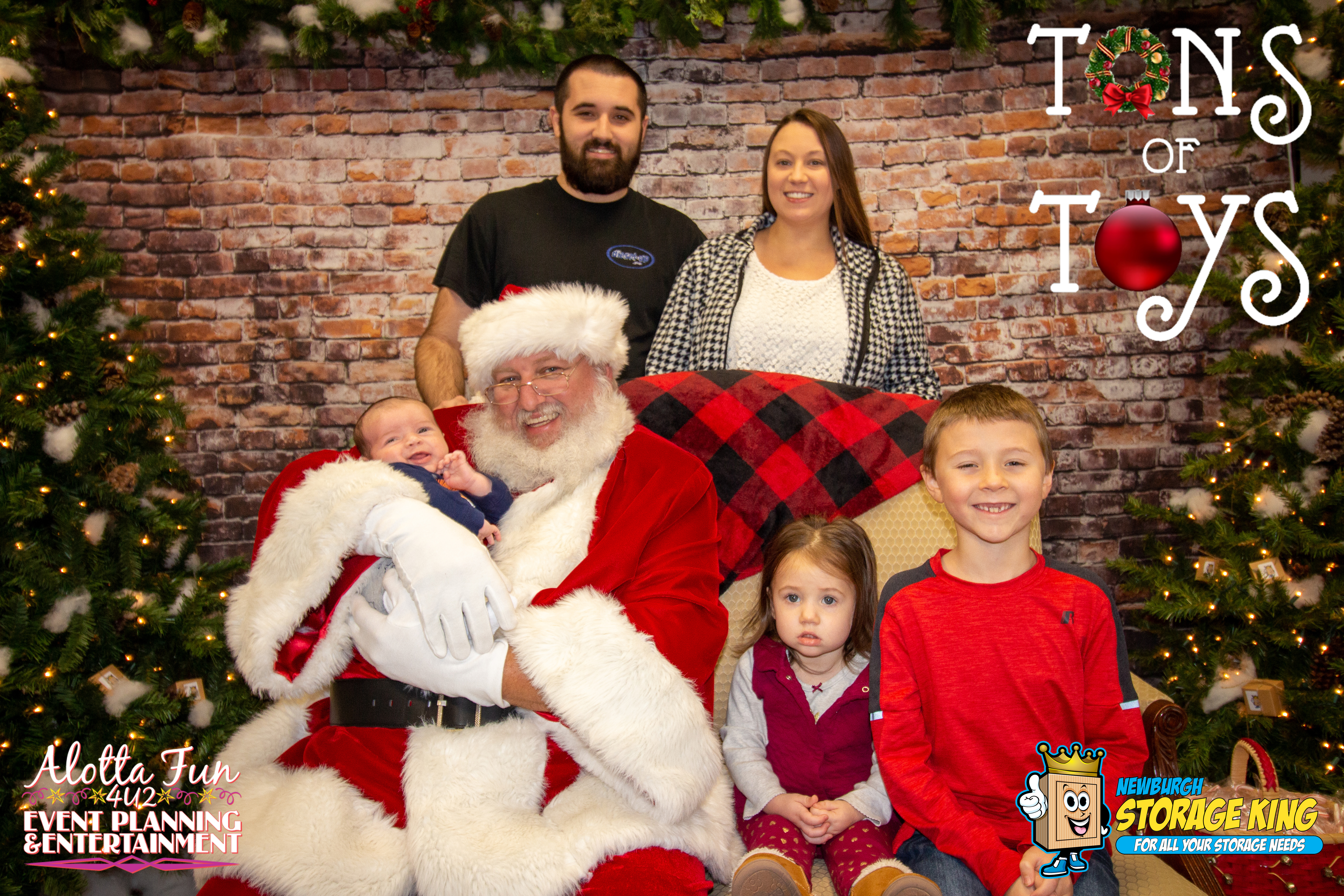 family posing with santa, two parents in background, two children sit next to Santa who holds a baby