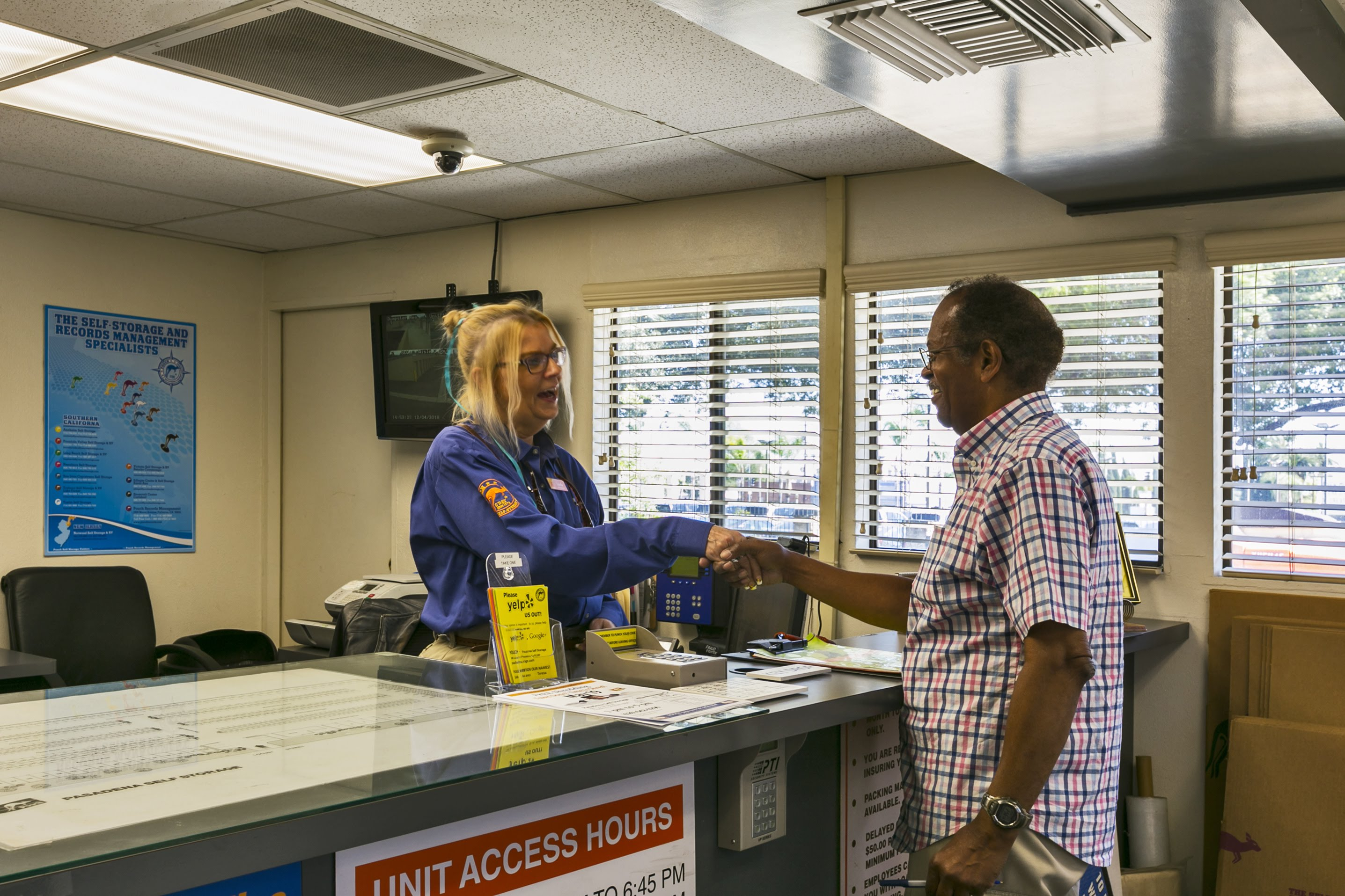 Interior office of storage facility, clerk shaking hands with customer