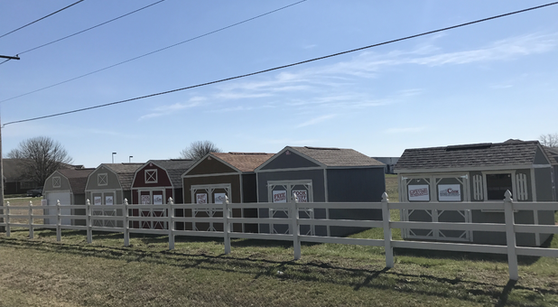 A row of storage sheds behind a wooden fence