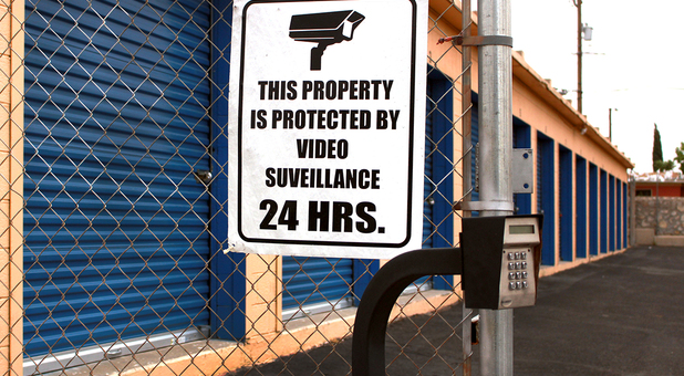 Security sign mounted to fence with storage building in the background