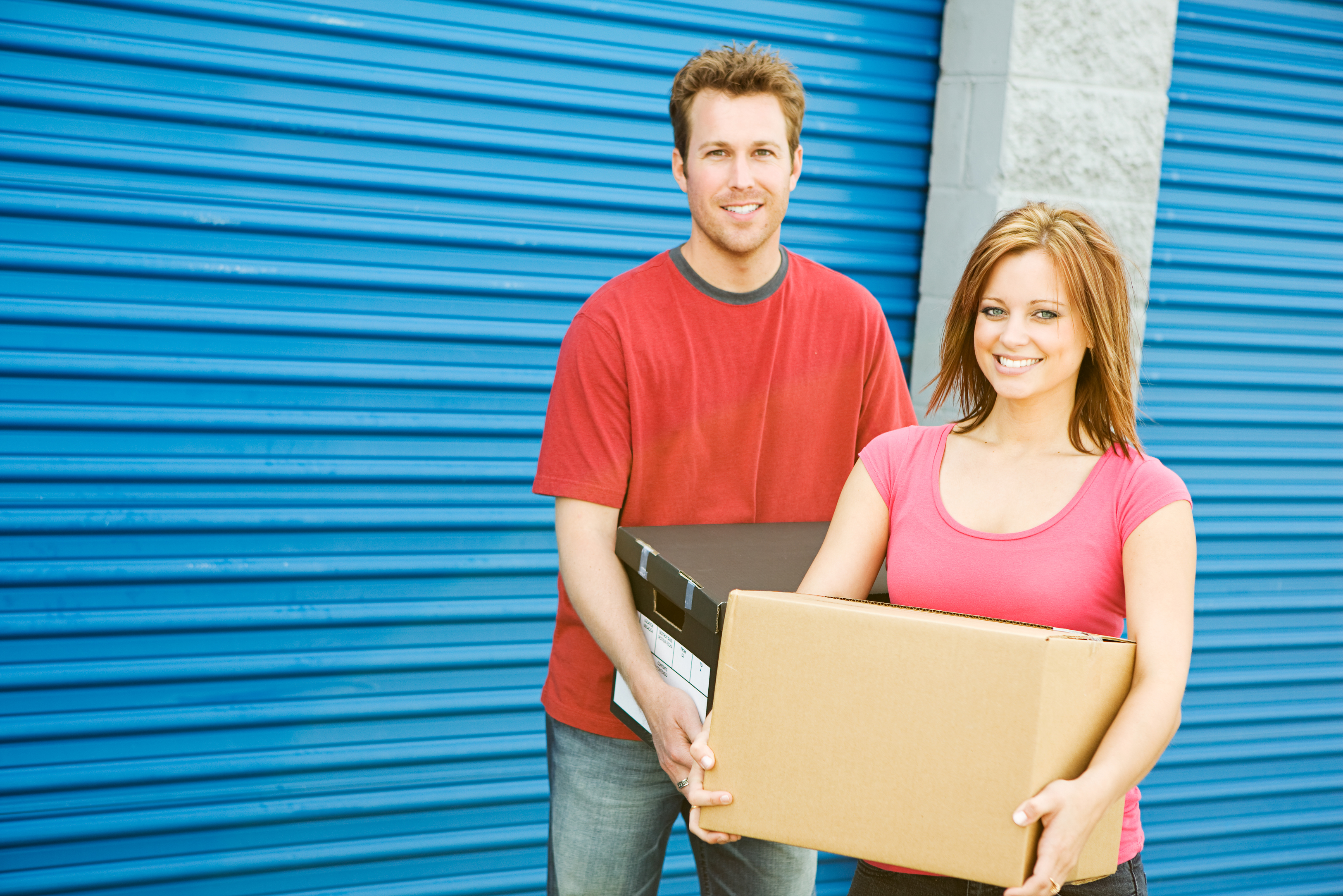 man and woman smiling and holding moving boxes