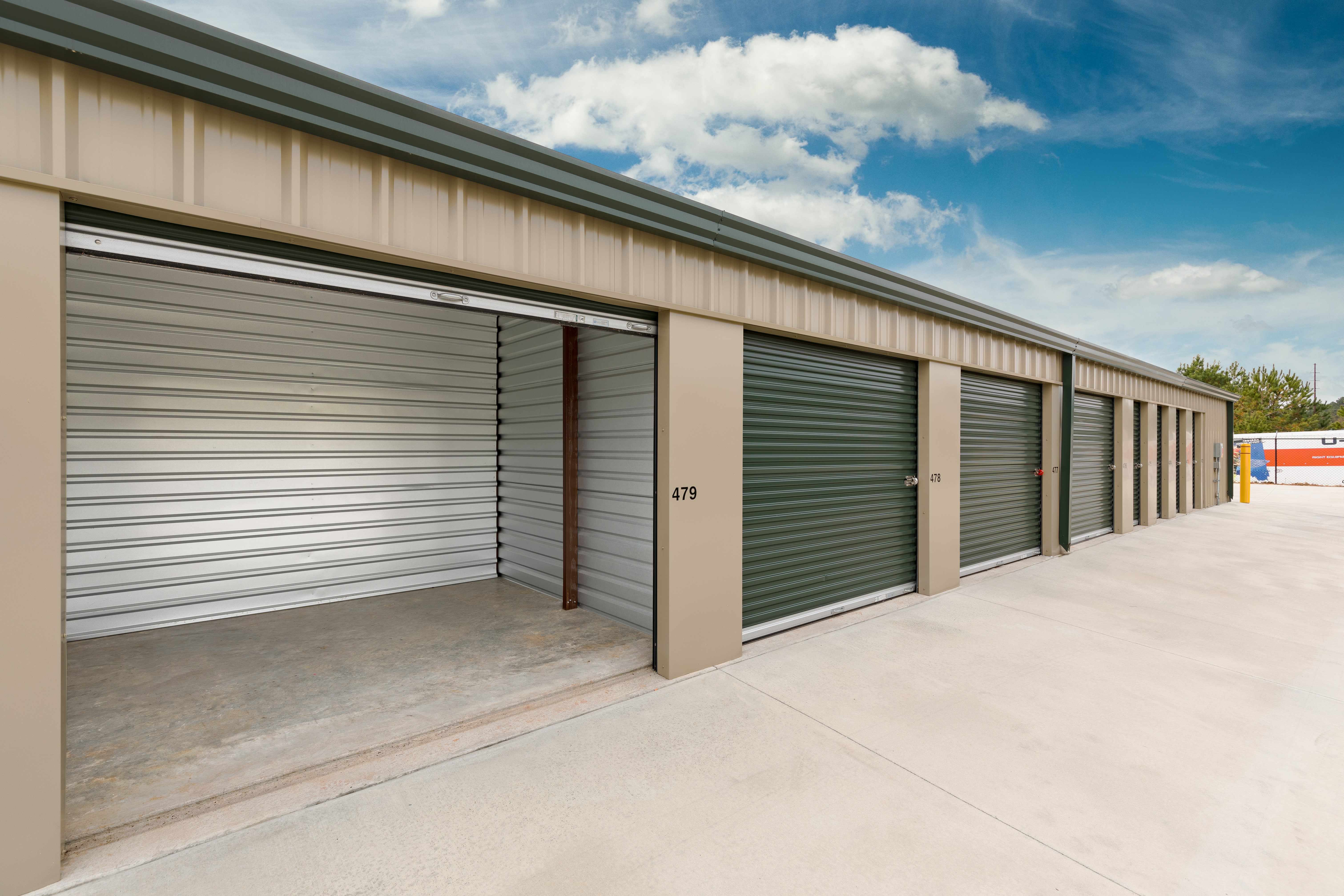 row of storage units, one with roll up door open