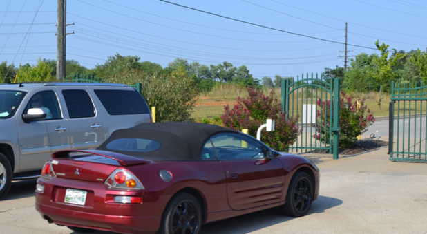Two cars near the front gate. The entry gate is open and one car has just passed through. Another car, to the right, waits for the exit gate to finish opening.
