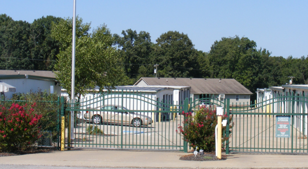 Automatic gate  with two sides, one for entry and one for exit. Both gates are shut. Bushes and shrubs conceal part of the fence connected to the gate. A car is parked in a row of parking spaces behind and to the right of the gates. Three storage buildings and one office are behind . Trees in the background.