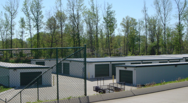Three buildings of exterior self storage buildings with drive up access doors. Several trees line the background, a parked moving trailer is parked near one of the buildings. There is a fence across part of the foreground, on a slight incline in front of the buildings.