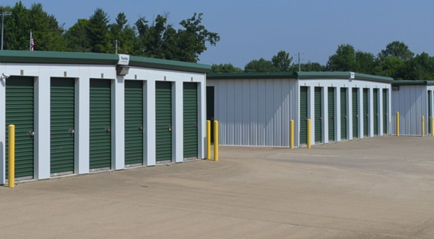 Three self storage buildings, each with unit doors facing left and traffic pillars around their corners