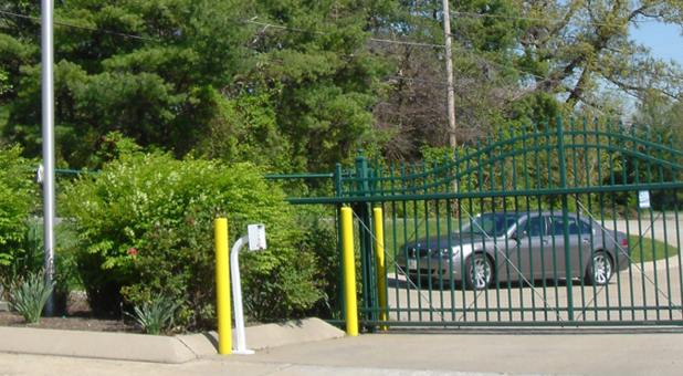 A 4-door sedan waiting behind a gate at the entrance to Excell Storage. A keypad is on the interior side of the gate