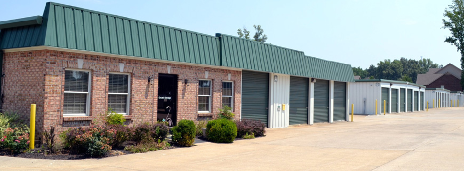 Excell Storage Front Office brick building with doors and windows facing right. Self Storage units are connected to the building