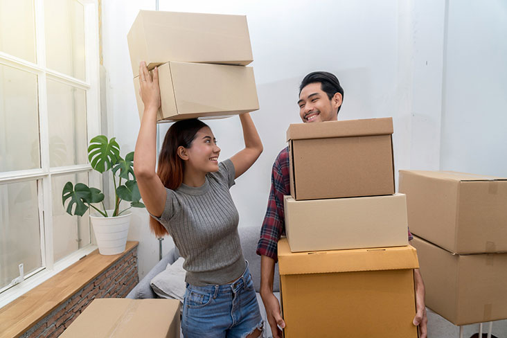Young couple packing boxes to put into self storage.