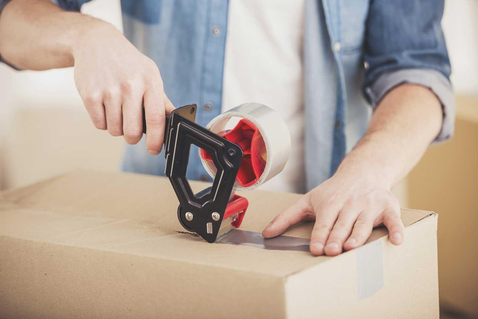 Un joven pone cinta de embalaje en una caja para poner en almacenamiento.