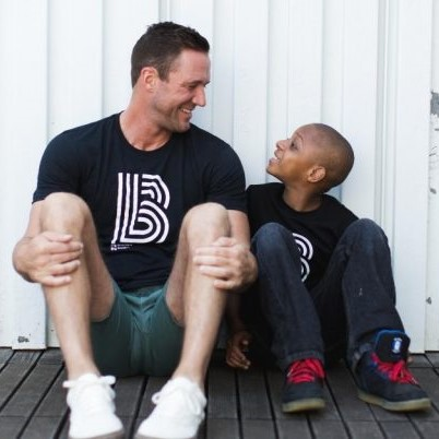 A man and child smiling at each other