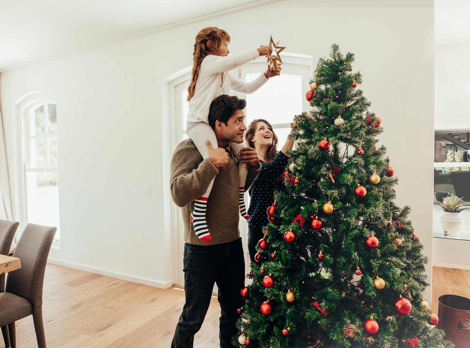 Una familia prepara su árbol de navidad para fiestas.