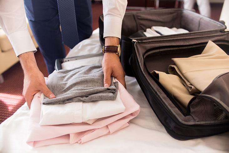 Hombre dobla camisas para prepararlas para almacenamiento.
