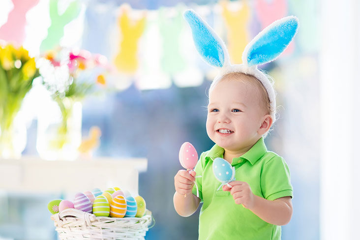 Little boy holds Easter decorations leading up to the Easter holiday.
