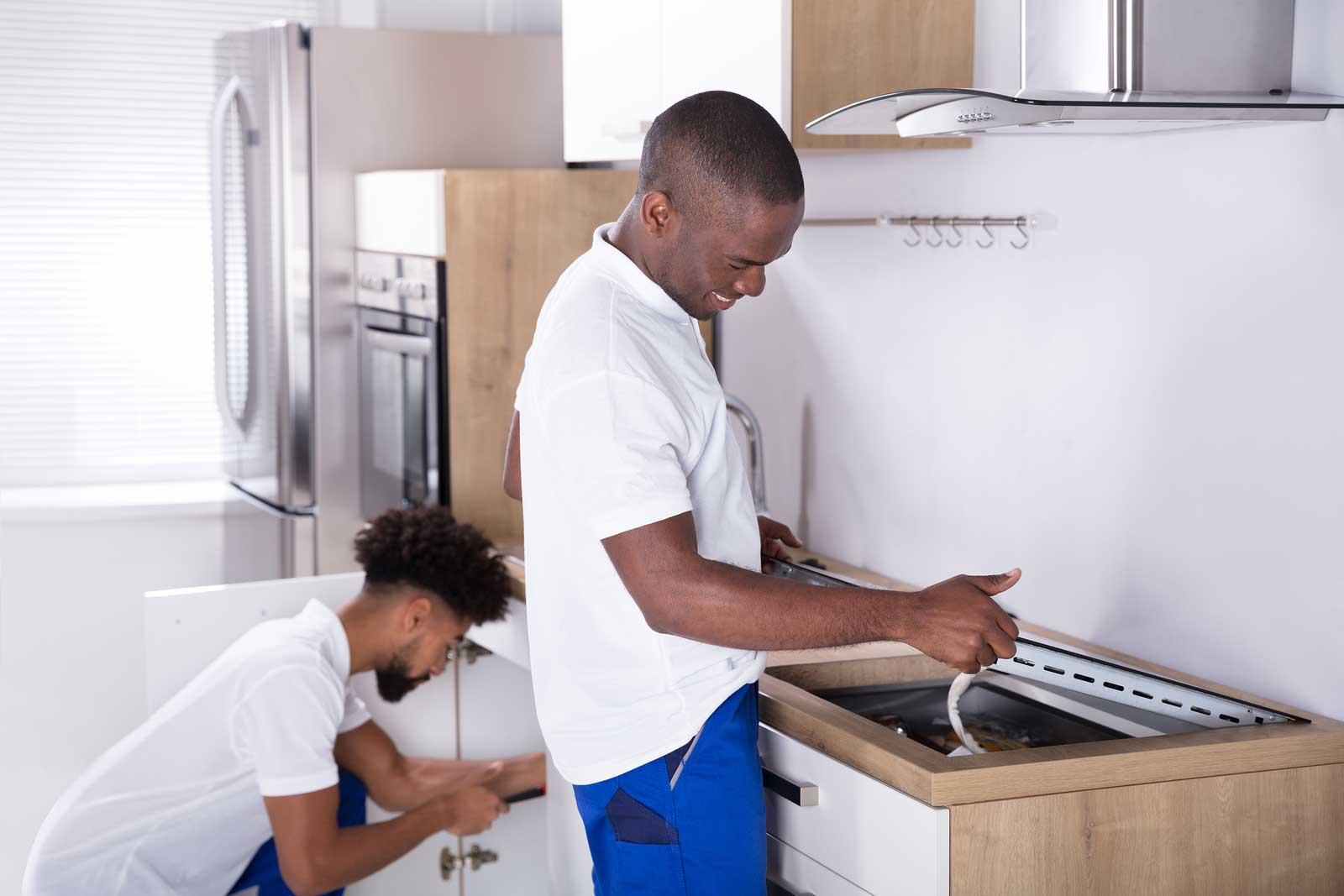 Dos hombres preparan una cocina y un horno para moverla al almacenamiento
