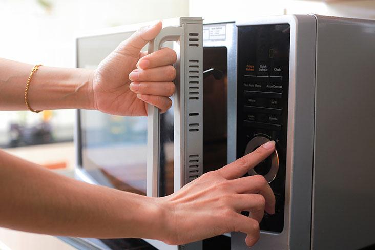 Une personne utilisant un micro-ondes dans la cuisine.