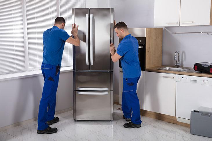 Dos hombres preparan un refrigerador para su almacenamiento.