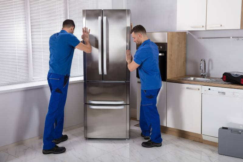 Two men prepare a refrigerator for self storage
