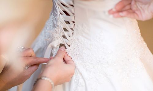 Buttoning up a wedding dress to wear on the big day