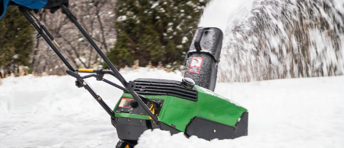 A man pushes a snow blower to clear his driveway