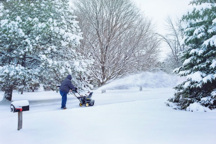 a man using his snowblower