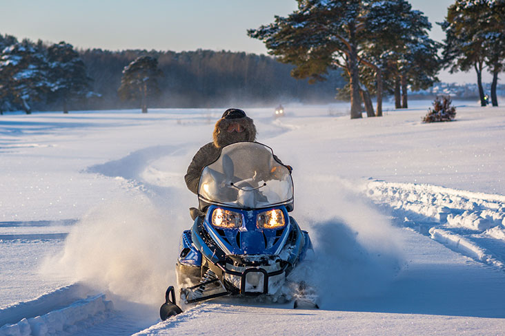 A snowmobile races through a snowy field.