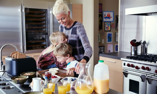 a mother makes breakfast with her children
