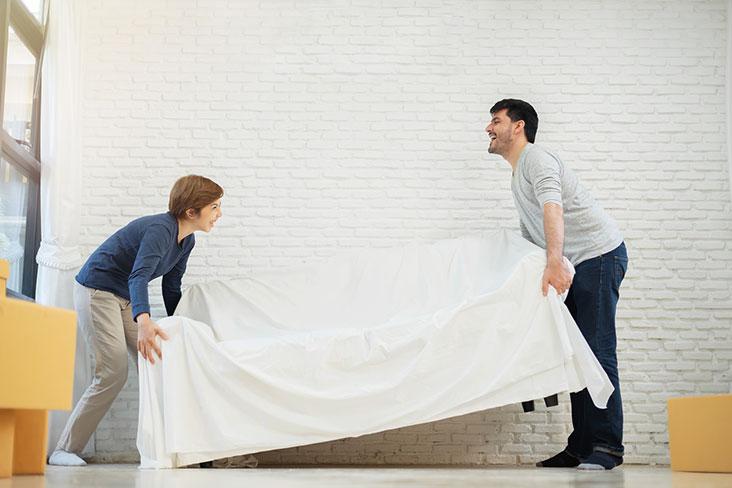 Hombre y niño mueven el sofá a una unidad de almacenamiento