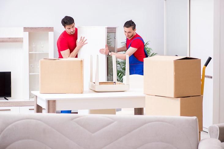 Trabajadores de empresa de mudanzas mueven cajas para preparar una mesa para su almacenamiento.