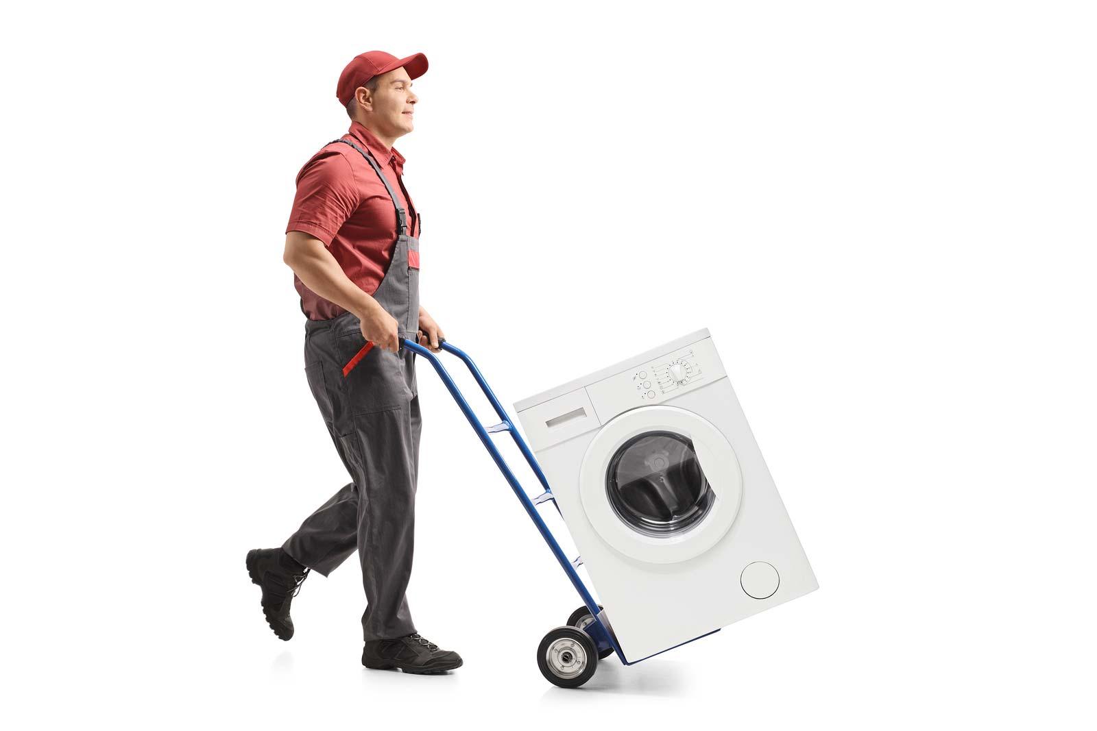Un homme transporte une machine à laver sur un chariot