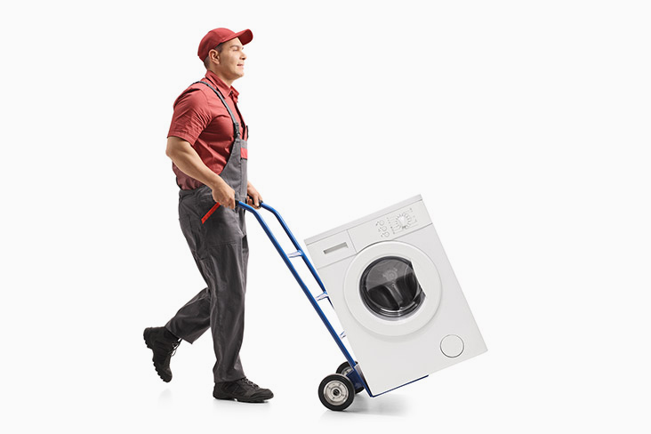 Man hauls a washing machine on a dolly