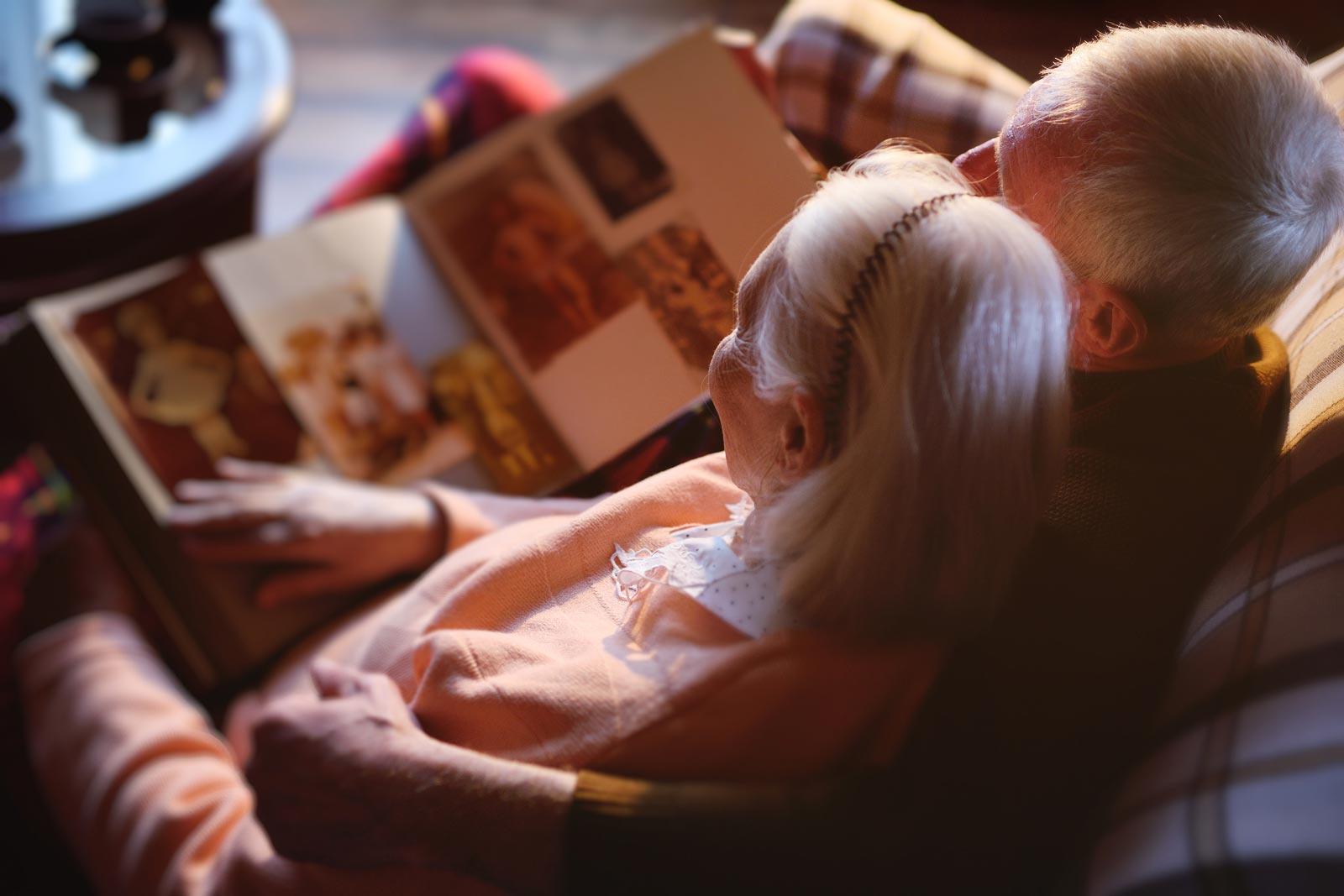 Un homme et une femme regardent leurs photos de famille dans un album avant de les mettre dans un mini-entrepôt