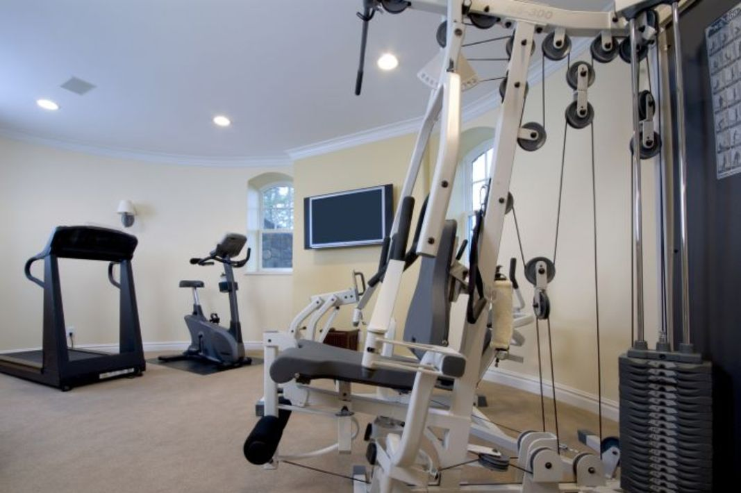 Home gym with treadmill, exercise bike and other equipment.