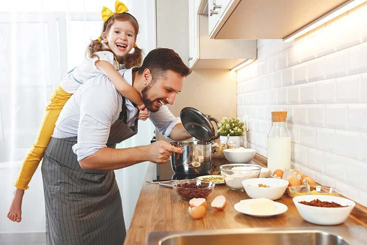 Family cooks with kitchen items prior to moving utensils into storage