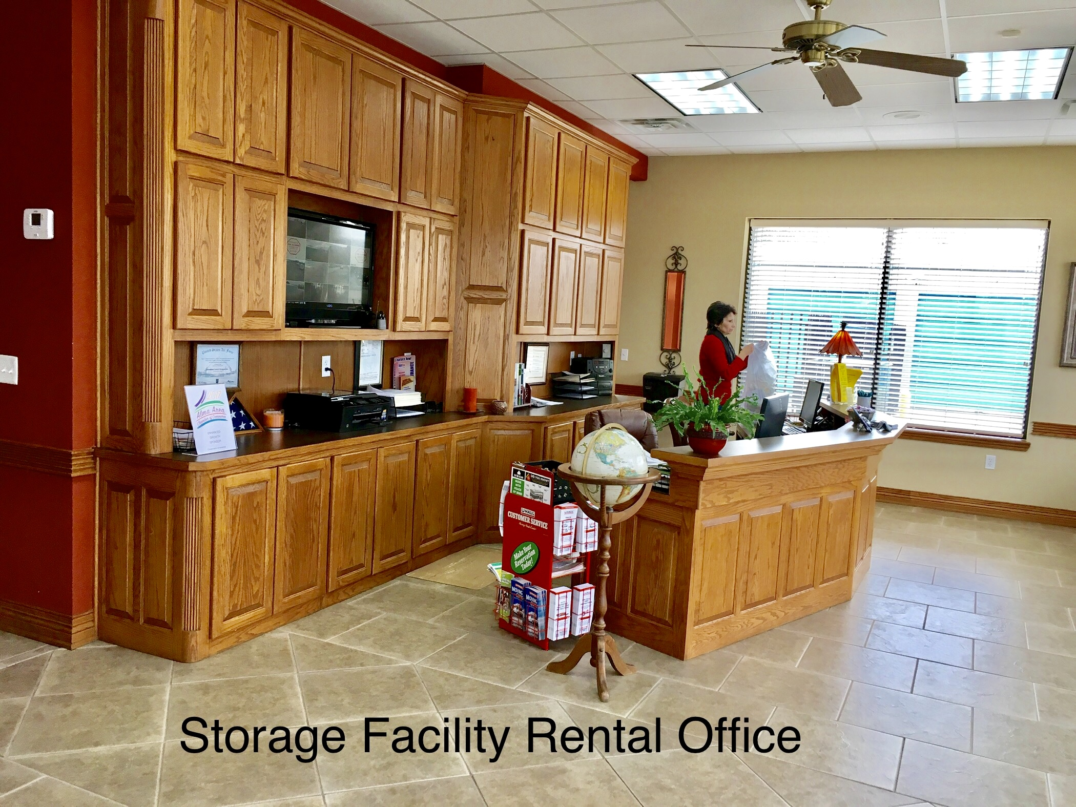 interior of storage facility rental office with manager standing behind desk