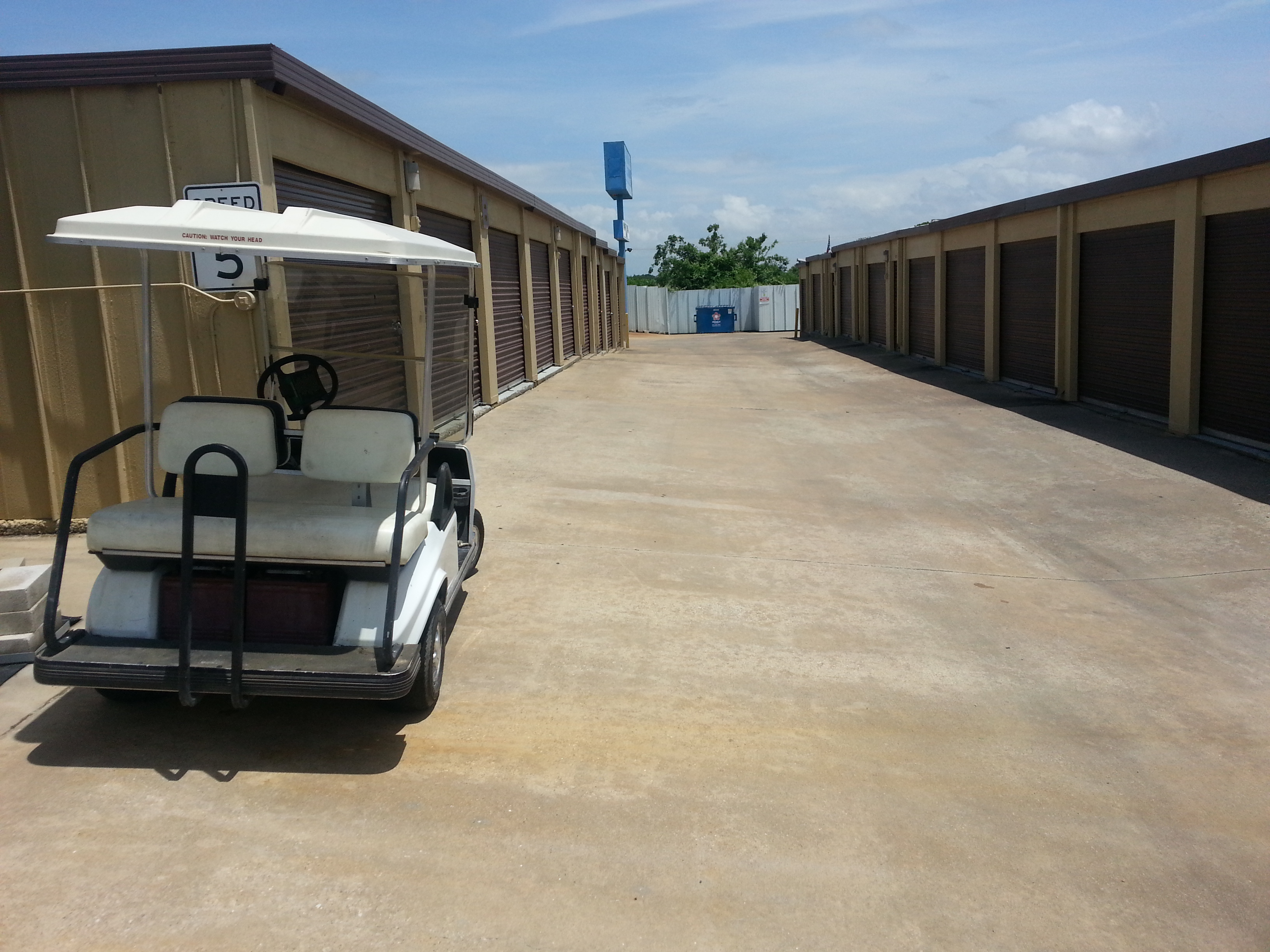 golf cart parked in front of storage buildings with drive up access
