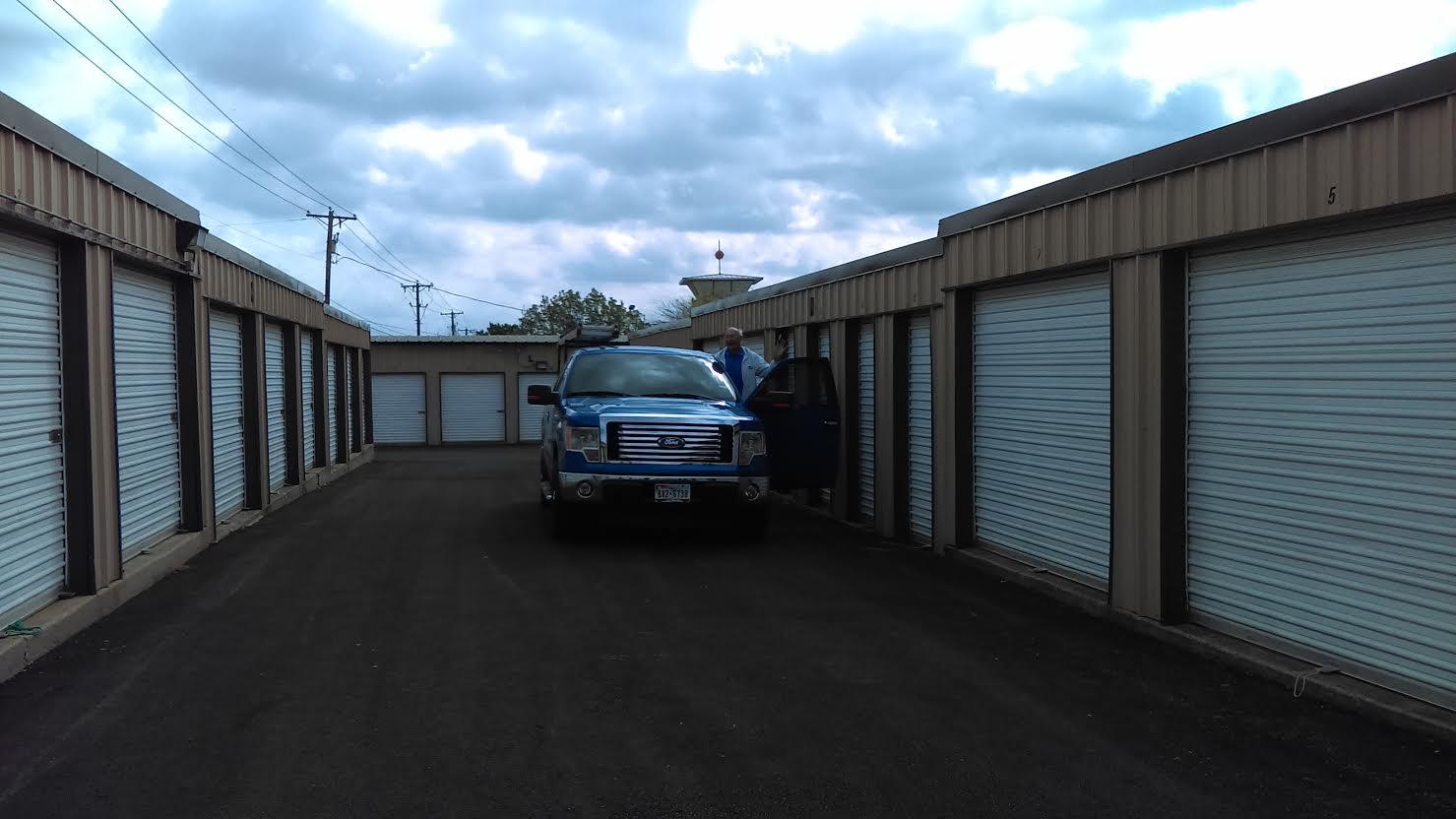 Car parked between storage buildings